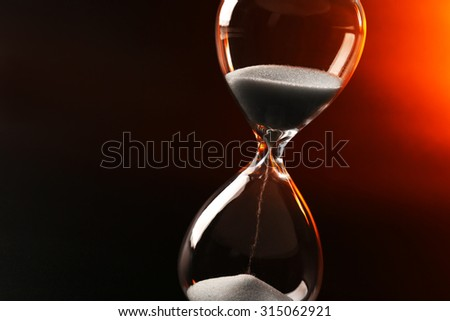 Hourglass on dark color background - stock photo