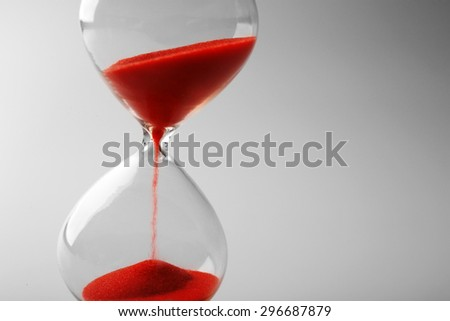 Hourglass on grey background - stock photo