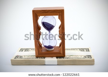 Hourglass on pile of paper money over  white background - stock photo
