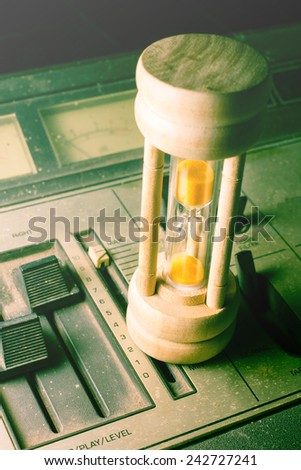 Hourglass on retro sound player or mixer - stock photo