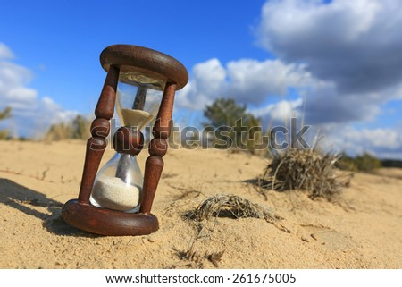 Hourglass on sand in nice sunny day