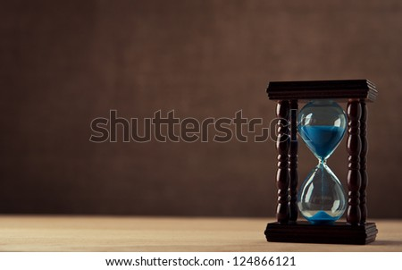 hourglass on wooden table - stock photo