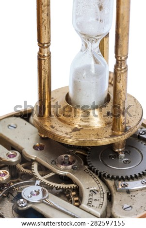 Hourglass standing on the open clockwork of a pocket watch selective focus on the sandglass  isolated on white background    - stock photo