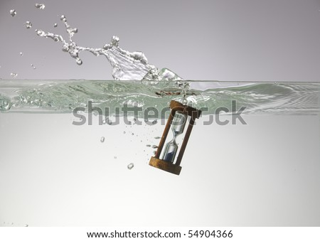Hourglass submerged into the water. - stock photo
