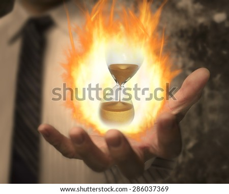 Hourglass with fire ball in the business man's hand - stock photo