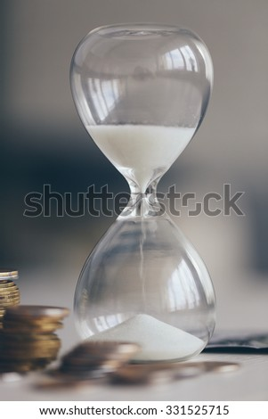 Hourglass with money on table on bright background