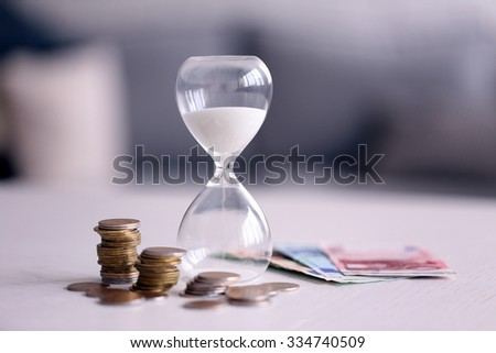 Hourglass with money on table on bright background - stock photo