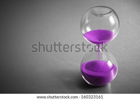 Hourglass with Purple Sand on Stainless Steel Background - stock photo
