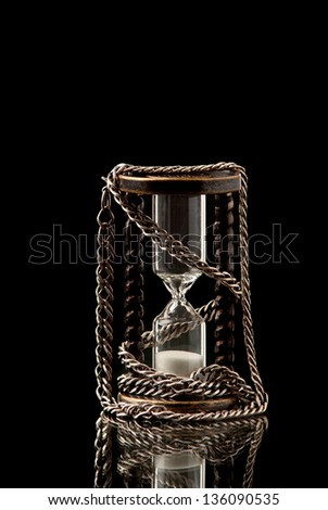 Hourglass with silver chain on black background. Studio shot.