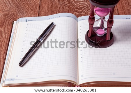 Hourglasses and book on a wooden table. - stock photo