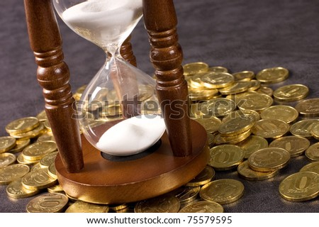Hourglasses and coin On a grey - stock photo