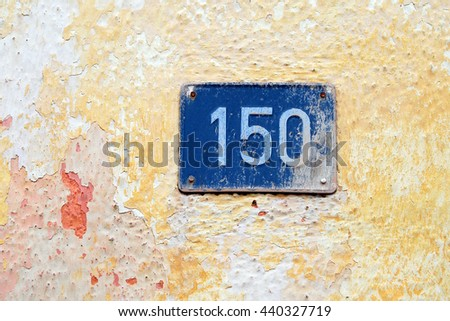 House address plate number (150) hanging on wall - stock photo