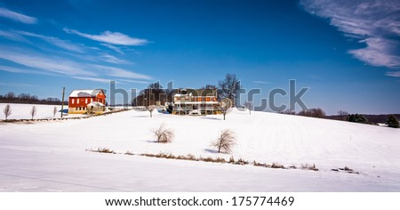 House and barn on snow covered farm fields in rural Carroll County, Maryland. - stock photo