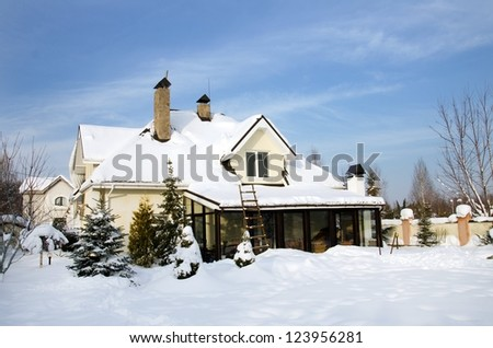 house and its garden under snow and blue sky in winter - stock photo