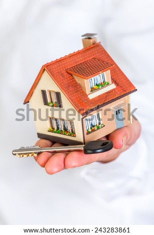 House and key in human hands on a white background