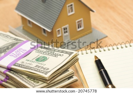 House and Money with Pad of Paper and Pen - stock photo