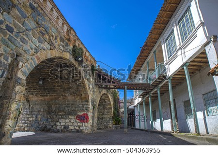 House and patio behind an old stone bridge, in Cuenca Ecuador