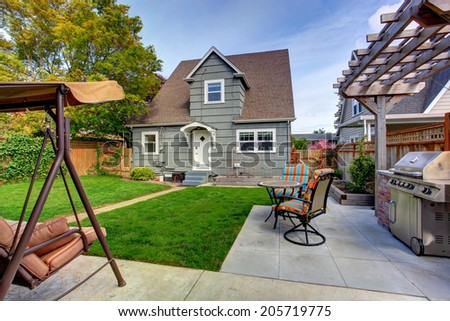 House backyard with small patio area and garden swing - stock photo