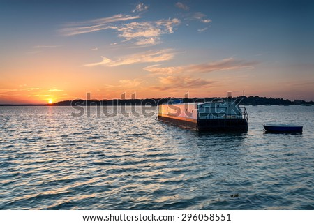 House boat at sunset afloat on Bramble Bush Bay at Studland on the dorset coast, looking out to Brownsea Island - stock photo
