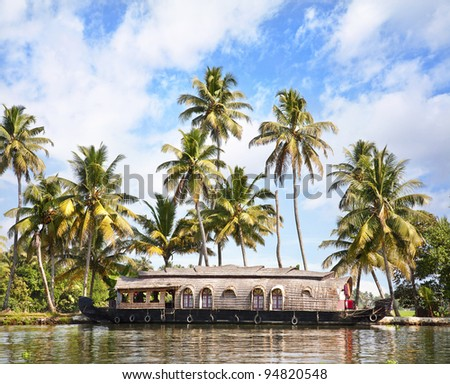 House boat in backwaters at palms background In alappuzha, Kerala, India - stock photo