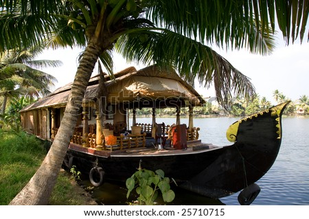 House boat in India over tropical palm on the river - stock photo