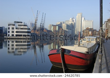 House boat moored in South Dock and Canary Wharf Skyline, London, England - stock photo