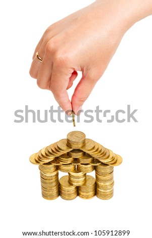 house built of coins female hand isolated on white background, top view - stock photo