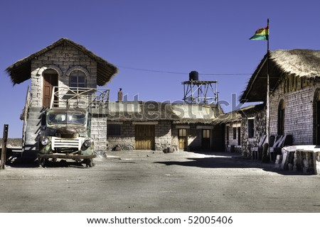 house built with salt in salar the uyuni bolivia old grunge car and bolivian flag - stock photo