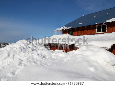 House buried in deep snow with a bright blue sky in the background.