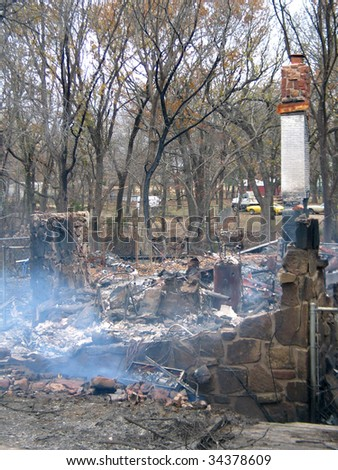 House burned to the ground, with smoldering ashes - stock photo
