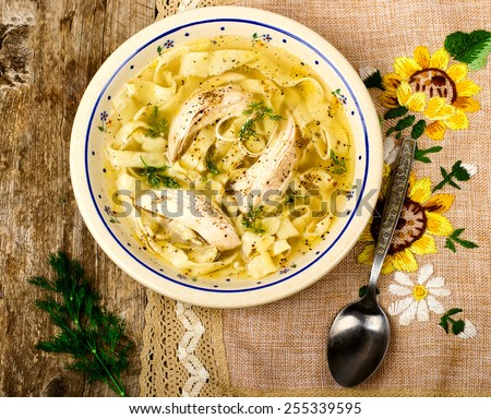 house chicken soup with handmade noodles on a wooden table. style rustic. selective focus - stock photo
