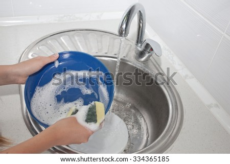 House chores - Washing the dishes on the kitchen sink - stock photo