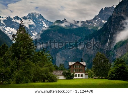 House close to a Steep Rocky Mountain in Switzerland - stock photo