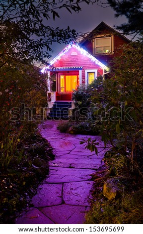 House decorated and lighted for Christmas and for New Year Eve . Night in Vancouver, Canada. Vertical. - stock photo