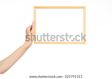House decoration and Photo Frame topic: human hand holding a wooden picture frame isolated on a white background in studio - stock photo
