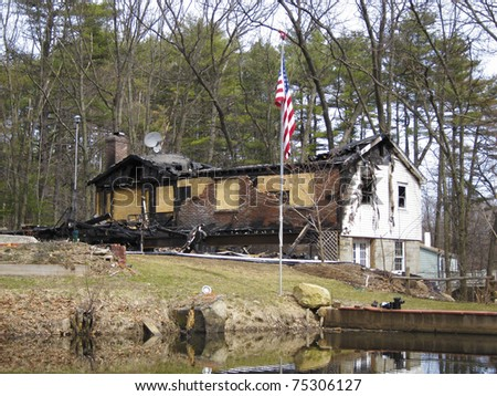 House destroyed by fire with American flag still on pole - stock photo