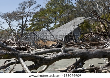house destroyed by flood surrounded by driftwood. - stock photo