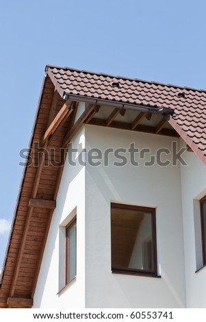 House detail against blue sky - stock photo