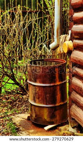house drain pipe and rusted barrel on the corner of the block country house - stock photo