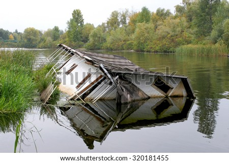 House drowning in the river. The concept  agency real estate insurance. - stock photo