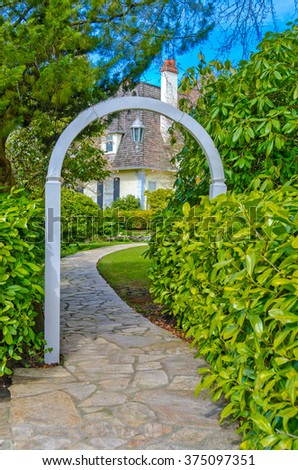 House entrance. Nicely paved doorway to the house through the wooden arch. Landscape design. - stock photo
