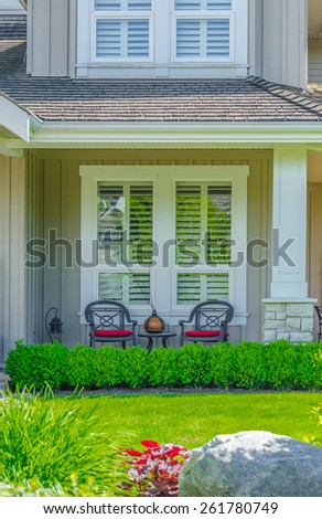 House entrance with nicely made, organized front porch and nicely trimmed and landscaped front yard. - stock photo