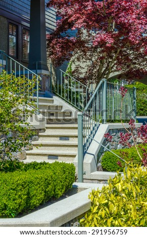 House entrance with nicely paved doorway, steps and handrails and trimmed and landscaped front yard. Vertical. - stock photo