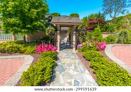 House entrance with the paved doorway the door and nicely trimmed and landscaped front yard. - stock photo