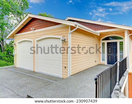 House exterior. Entrance porch with black door  and railings. House with two car garage - stock photo
