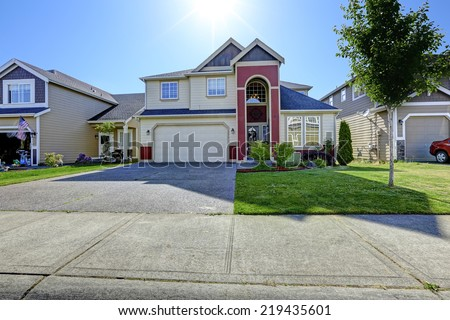 House exterior. High entrance porch in red trim and garage with driveway