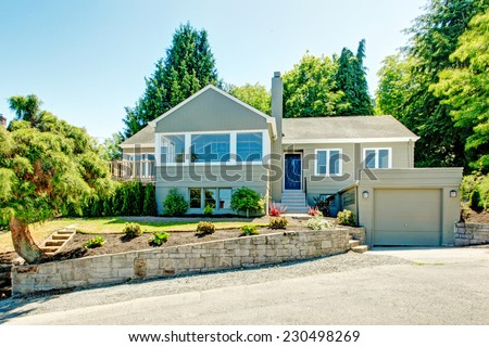 House exterior in clapboard siding. House with garage, driveway and front yard landscape - stock photo