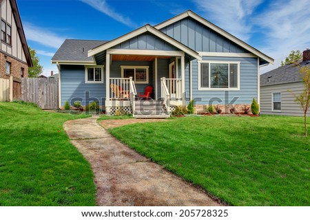 House exterior. View of front yard and small entrance porch with chairs - stock photo