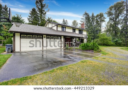 House exterior. View of landscape on front yard. Countryside house with garage