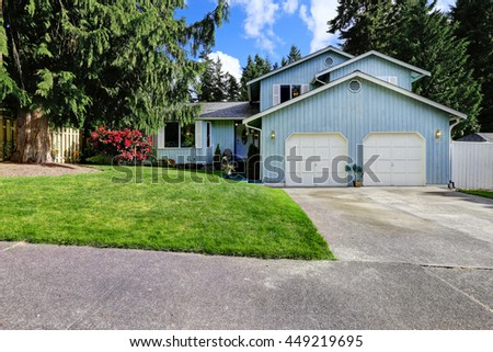 House exterior with big fir trees around. Classic American blue house with two garage spaces and driveway.  - stock photo